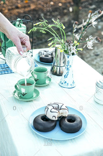 Woman pouring fresh milk from jug to ceramic mug while having picnic in garden