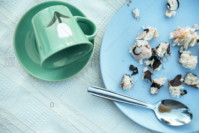 From above empty green ceramic mug dropped on saucer and blue round plate with small crumbs of tasty pastry in composition with dirty metal teaspoon after breakfast