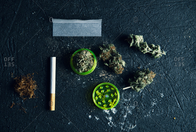 Top view of dried cannabis buds and rolling paper with cigarette on grunge surface