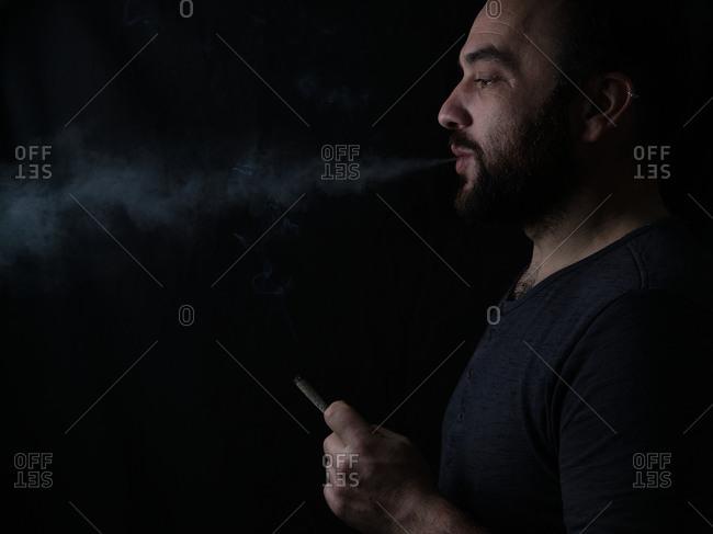 Adult man smoking cannabis joint