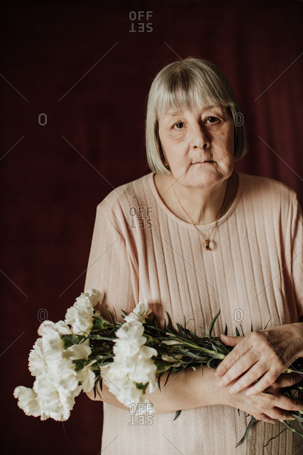 From above thoughtful old female with gray hair looking at camera and holding bouquet of white carnation at home