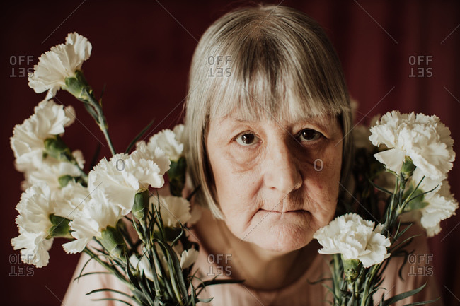 From above thoughtful old female with gray hair looking at camera holding bouquet of white carnation at home
