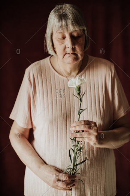 From above thoughtful old female with gray hair with closed eyes holding bouquet of white carnation at home