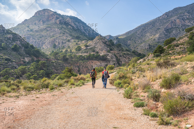 Back view of unrecognizable travelers walking through mountain location in summer day