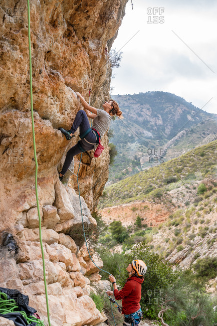 Fearless young females alpinist ascending on vertical cliff in mountain location in summertime