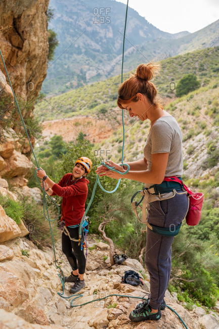 From above active young climbers adjusting equipment and tying rope while standing on rocks