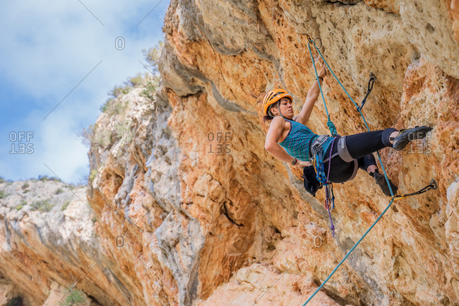 Fearless young female alpinist ascending on cliff in mountain location in summertime