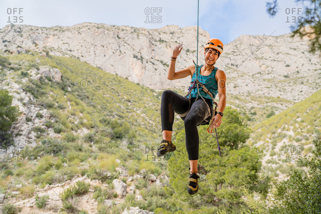 Cheerful athletic female alpinist looking at camera while hanging on cliff under cloudy sky
