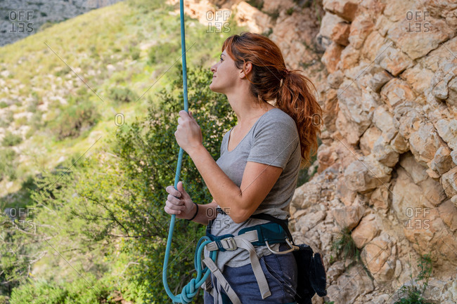 Confident young female climber checking rope before ascending cliff in summer day