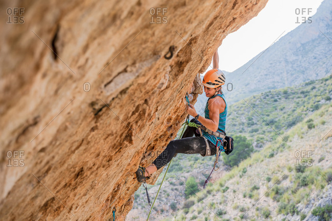 From below side view of active focused youthful female alpinist climbing on cliff in summer day