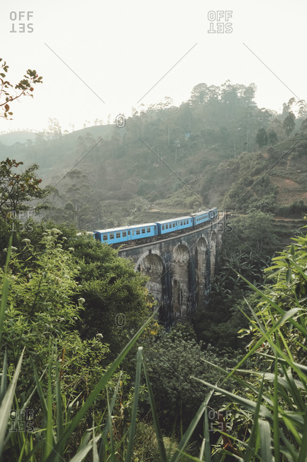 From above of blue train on stone bridge among tropical green jungles in foggy weather in Sri Lanka Asia
