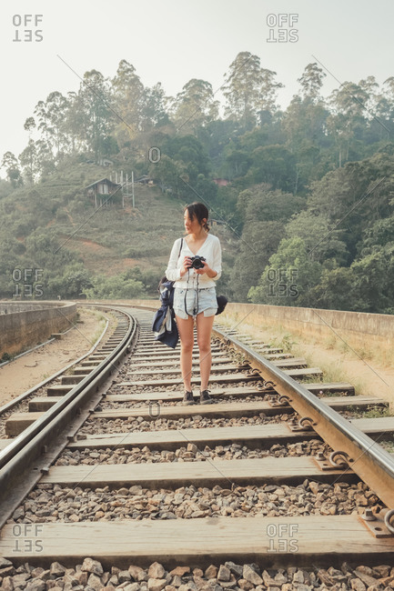 Female tourist walking on lonely railway against exotic forest