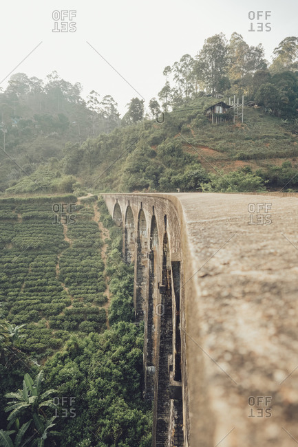 Brown stone surface of old bridge above green plantations with overgrown mountains on background in Sri Lanka Asia