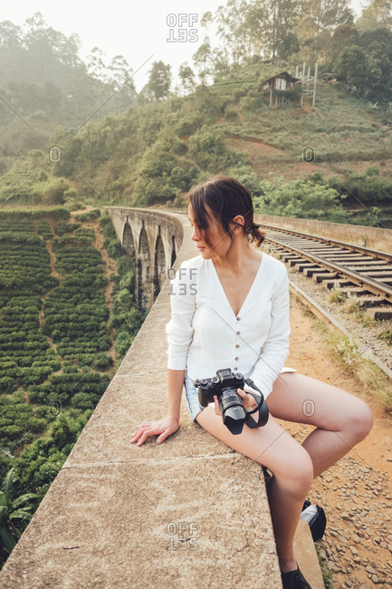 Young Asian woman on vacation taking photo with camera in nature