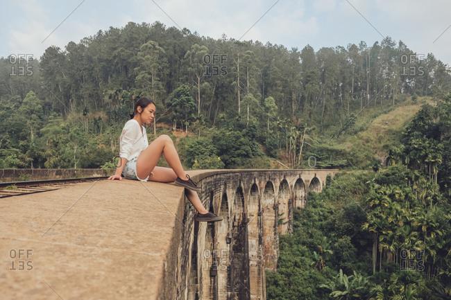 Asian woman sitting on railroad on bridge in tropical landscape