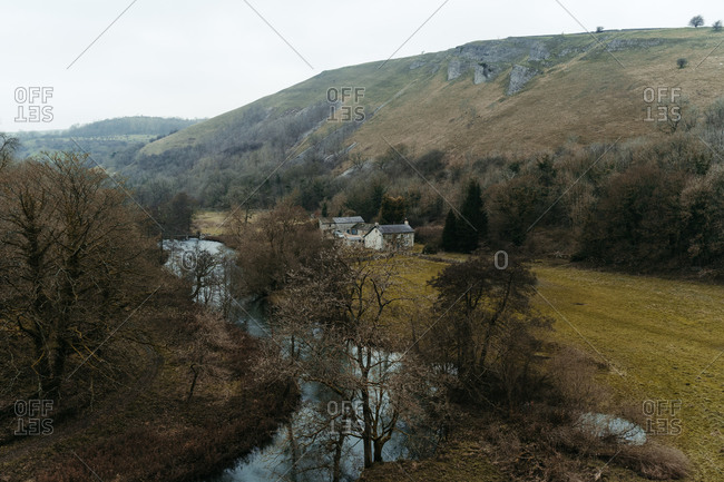 From above small river streaming between dry valley with trees and houses in mountain place in United Kingdom