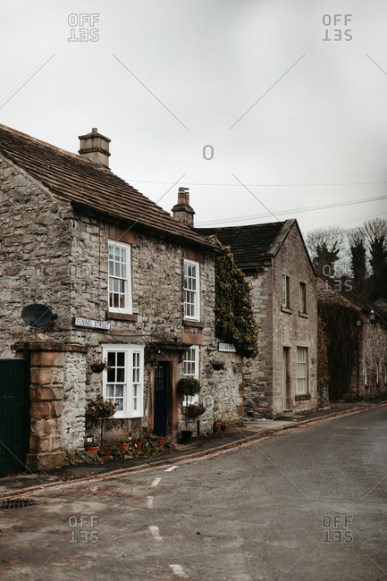 Ancient old cottages with white windows and empty asphalt road under cloudy sky in United Kingdom