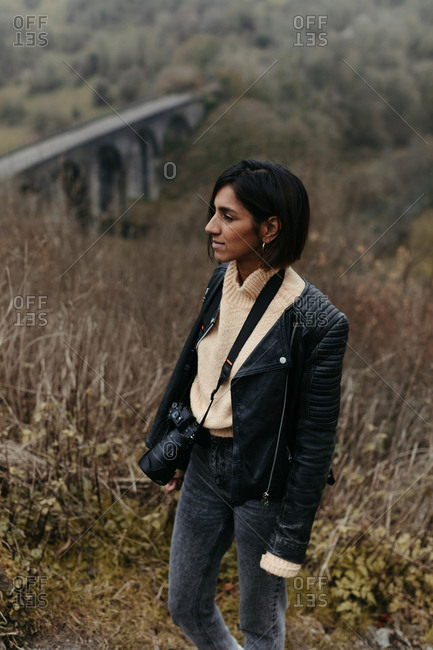 Thoughtful touristic woman with camera in stylish black leather jacket walking in valley with dry grass and old bridge in United Kingdom
