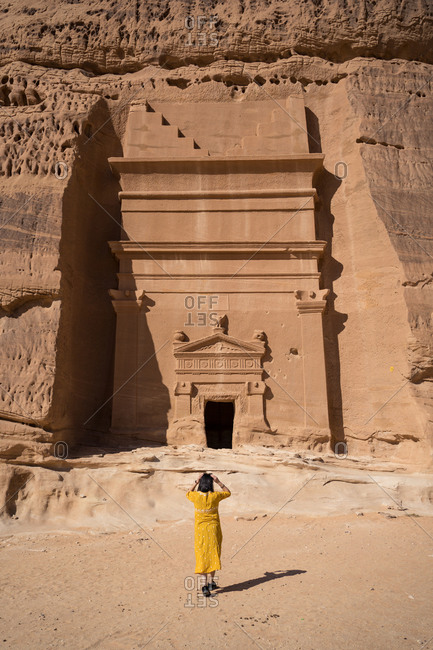 Back view of unrecognizable woman traveler standing near tombs carved into cliffs in Madain Saleh in Saudi Arabia