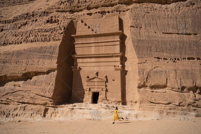 Happy woman traveler walking near tombs carved into cliffs in Madain Saleh in Saudi Arabia