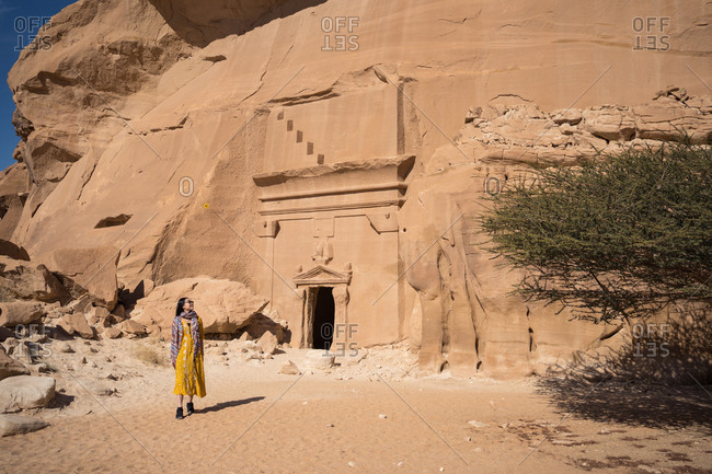 Happy woman traveler standing near tombs carved into cliffs in Madain Saleh in Saudi Arabia
