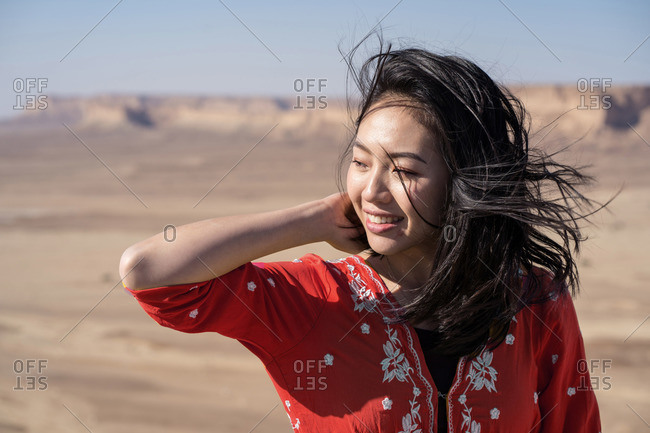 Happy youthful ethnic female tourist in red tunic visiting the Edge of the World in Saudi Arabia