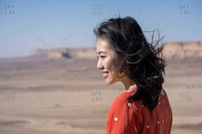 Side view of happy youthful ethnic female tourist in red tunic visiting the Edge of the World in Saudi Arabia