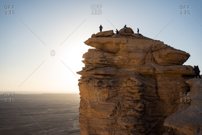 From below group of anonymous travelers contemplating colorful sundown while visiting the Edge of the World in Saudi Arabia