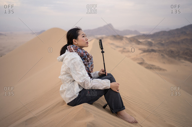 Side view of pensive young ethnic female tourist contemplating natural landscape while sitting on sandy dune in desert in Saudi Arabia looking away