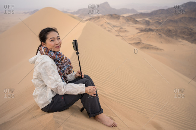 Side view of pensive young ethnic female tourist contemplating natural landscape while sitting on sandy dune in desert in Saudi Arabia looking at camera smiling