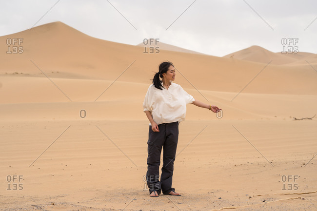 Happy youthful Asian woman looking away smiling while standing in middle of sandy desert in Saudi Arabia