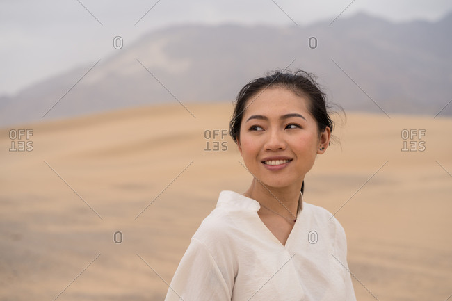 Side view of happy youthful Asian woman looking away smiling while standing in middle of sandy desert in Saudi Arabia