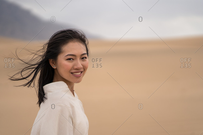 Side view of happy youthful Asian woman looking at camera while standing in middle of sandy desert in Saudi Arabia
