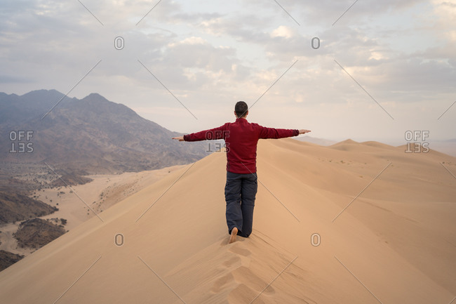 Back view of unrecognizable happy man with arms raised in casual clothes standing on dune during tour to desert in Saudi Arabia
