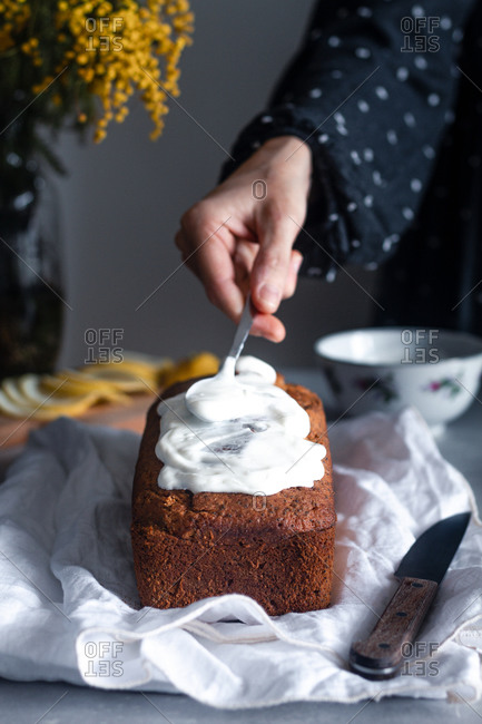 Crop hand of housewife decorating delicious homemade lemon and poppy seeds sponge cake with whipped cream at table with bouquet of mimosa flowers in background
