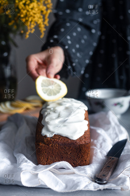 Crop hand of woman putting slice of lemon on yummy fresh homemade cake covered with whipped cream placed on white cloth on kitchen table with bouquet of mimosa flowers in background