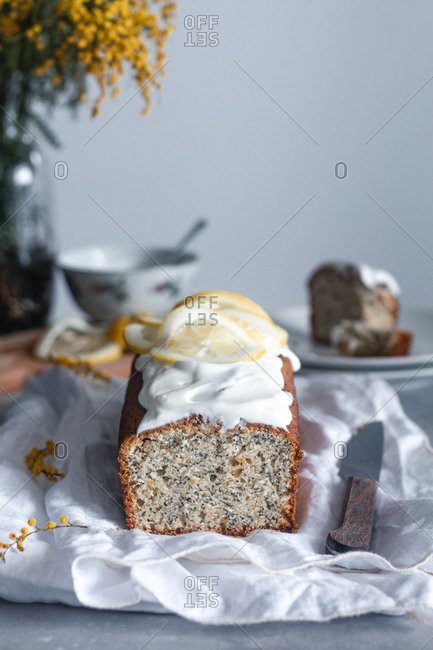 Cut appetizing aromatic freshly baked sponge cake with lemon and poppy seeds decorated with icing and slices of fresh lemon placed on white cloth with knife on table with flowers in background