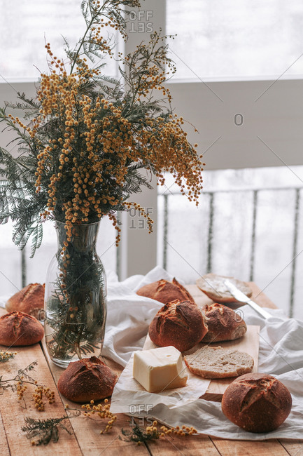 From above of homemade round rye bread and butter on wooden table with vase of aromatic mimosa flowers in soft daylight