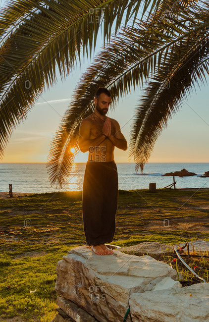 Calm shirtless and barefoot male sportsman standing and folding hands in front of chest on rocky fence with leafs of palm and tropical seashore on background during sunset