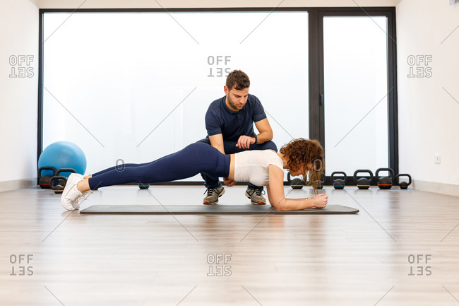 Side view of strong woman in plank position with male personal trainer in modern gym