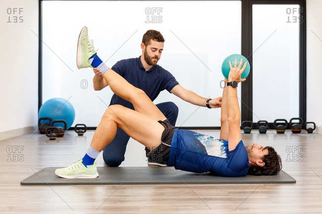 Side view of man in active wear lying on mat with one raised leg and hands with small ball under control of fitness trainer in gym