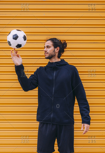 Young bearded male soccer in dark blue sports hoodie and shorts spinning ball on finger while standing against yellow roller shuttle background
