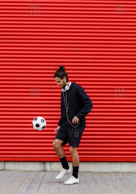 Man playing soccer ball on street