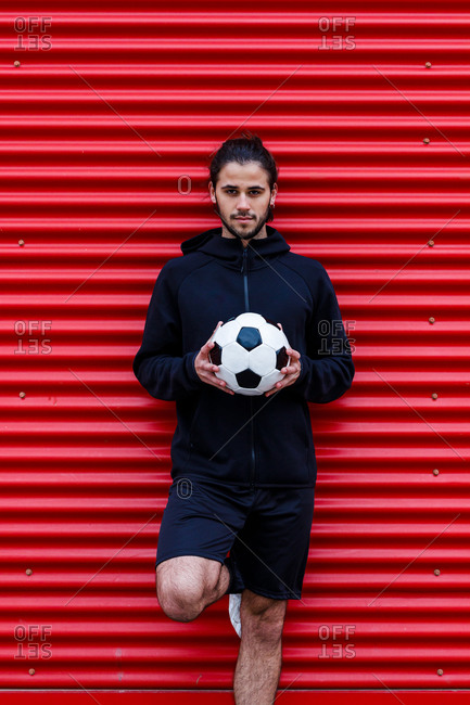 Man standing with ball on street