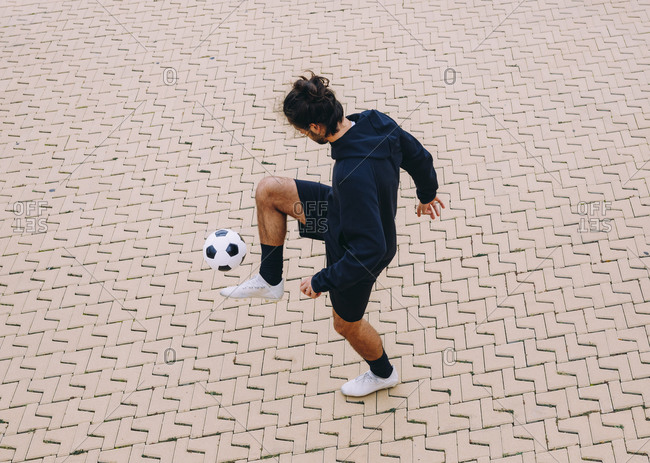 Sportsman kicking soccer ball with knee