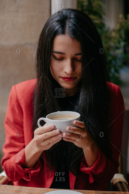 Pretty woman sitting at small wooden table holding a cup of fresh coffee during breakfast in a cafe