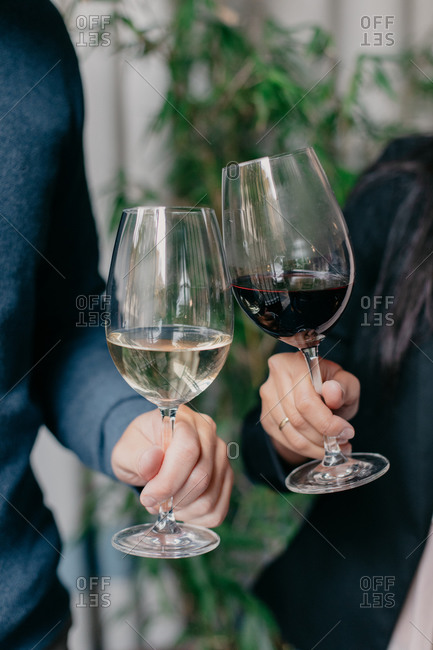 Cropped unrecognizable romantic affectionate couple toasting with glasses of wine and holding hands while sitting at wooden table in cozy cafe