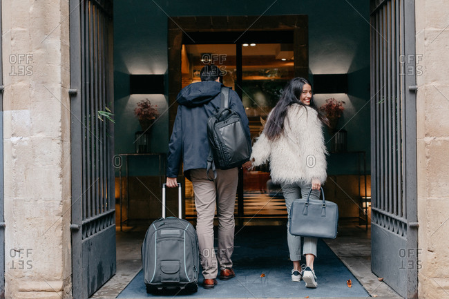 Back view of happy stylish young couple in love with suitcase and bags holding hands and entering modern city hotel during travel while woman looking at camera over shoulder