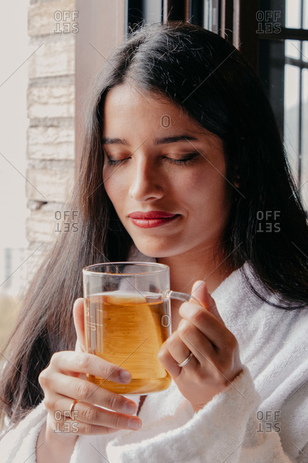 Tranquil calm young brunette female in white bathrobe standing next to window and enjoying hot tea in morning with closed eyes