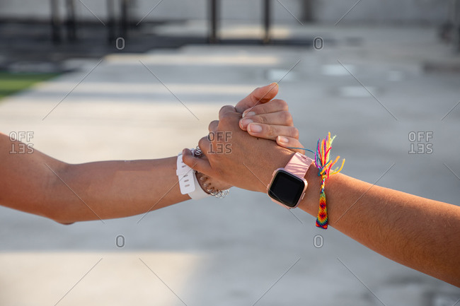 Crop hands of females with pink and white modern smartwatches giving high five and shaking hands on street with blurred background